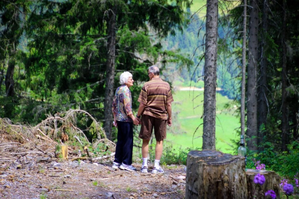 Elderly couple holding hands on a hike
